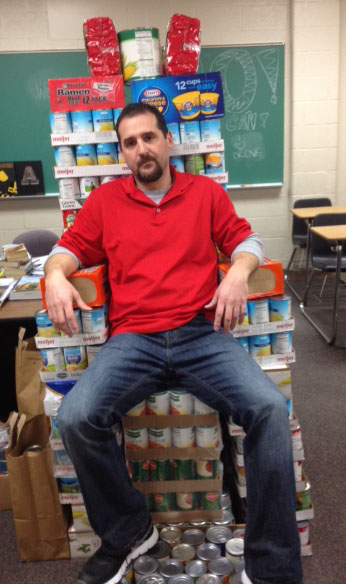 Mr. Lovalvo, the English Department's victorious tribute, sits atop a throne of cans his classes have collected.