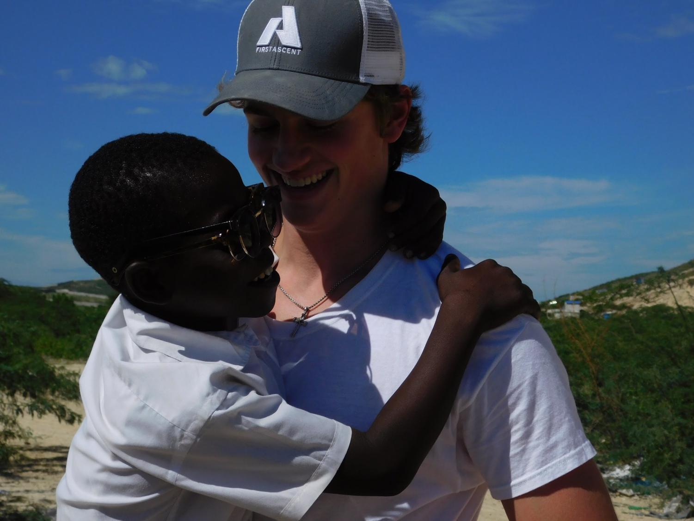 Michael Zyrek entertains Haitian child in the village of Turpin.