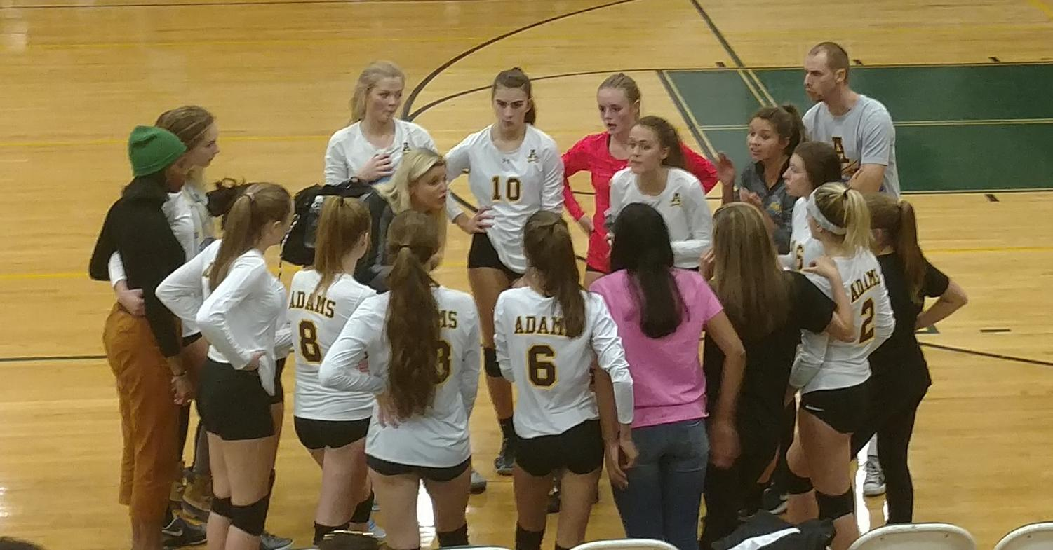 The volleyball team in the huddle right before the third game.