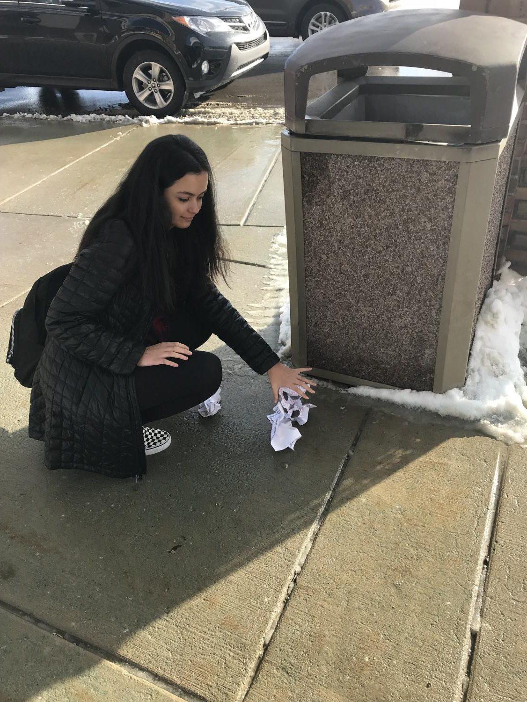 Brina Golubovic picking up trash outside of Adams High School.