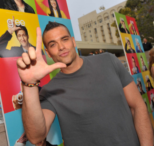 Salling, while still acting on Glee, during a concert doing the show's trademark hand gesture.