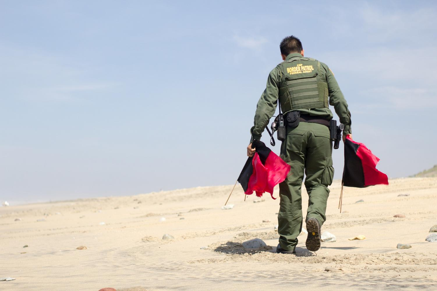 A US border patrol agent marking the border in a barren desert with red flags.