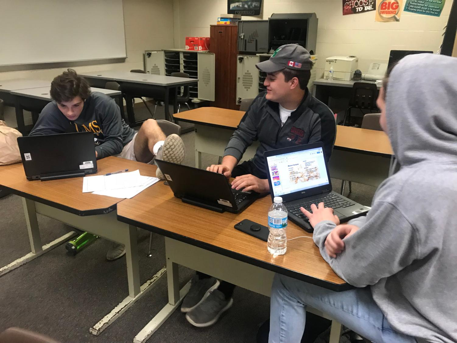 Juniors Carlo Munaco and Domenico Munaco and senior Christian Vataj in their Advanced Marketing and Advertising class utilizing their school-provided technology.