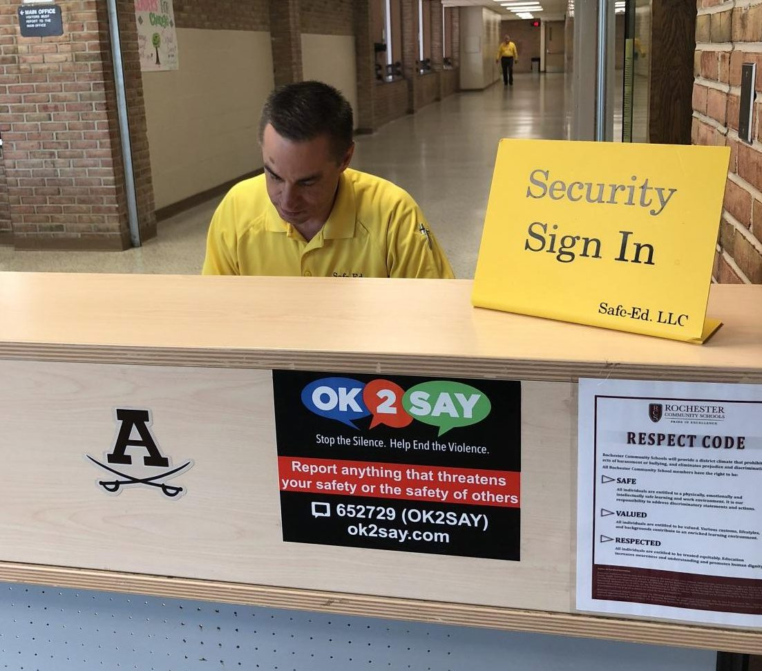 Adams security guard signing in students coming into the school ensuring a safe learning environment.