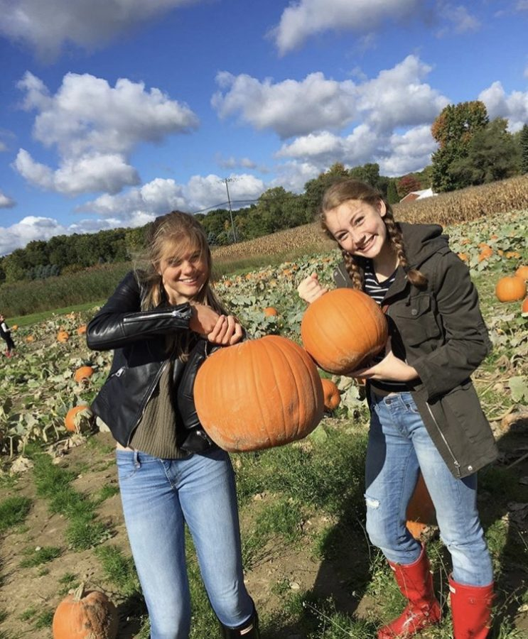 Seniors+Claire+Sanford+and+Charlotte+Schmidt+picking+pumpkins+at+the+Rochester+Cider+Mill.