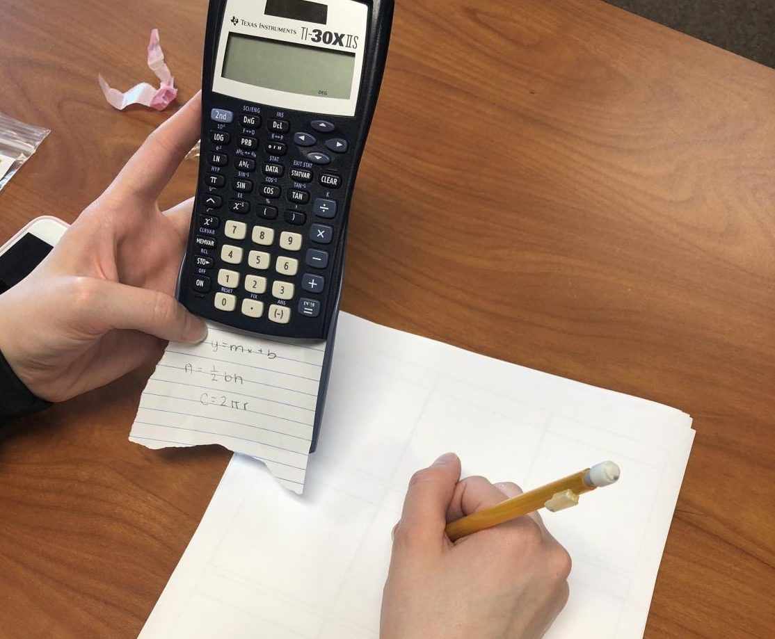 Student using a cheat sheet during a math quiz.