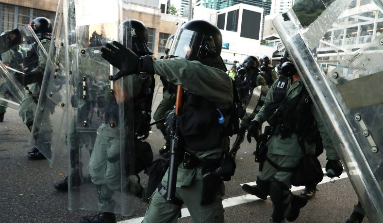 Hong+Kong+police+in+formation+containing+the+protesters.