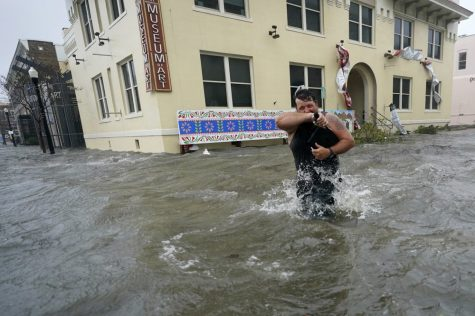 Man is walking through the streets with water levels well above the knees.