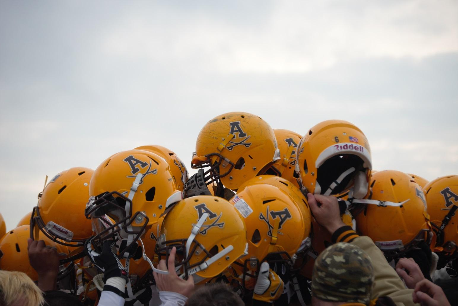 The football team raises their helmets after their loss to Clarkston.
