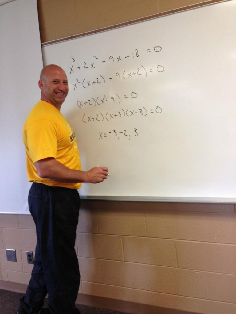 Mr. Hall writes a problem on the board. The new grading scale will especially effect the math department.