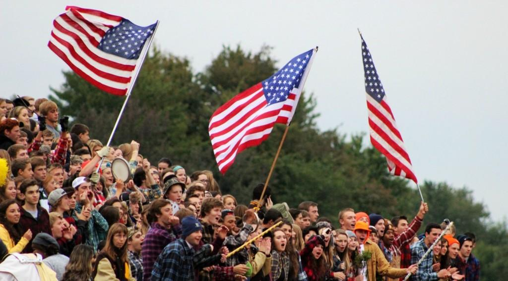 The AHS student section waves American flags during the national anthem at a football game.