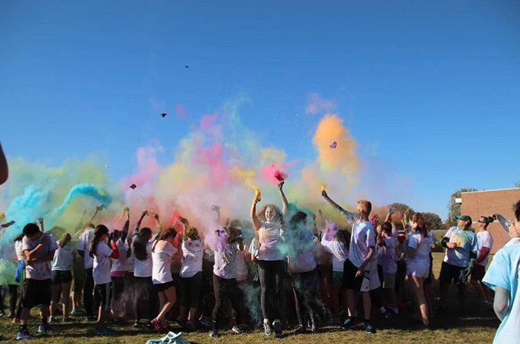 The+runners+throw+colored+chalk+into+the+air+at+the+end+of+the+color+run.