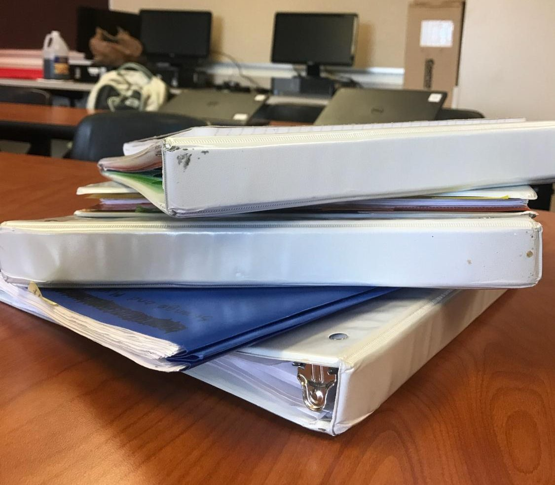 A stack of binders that could be donated.