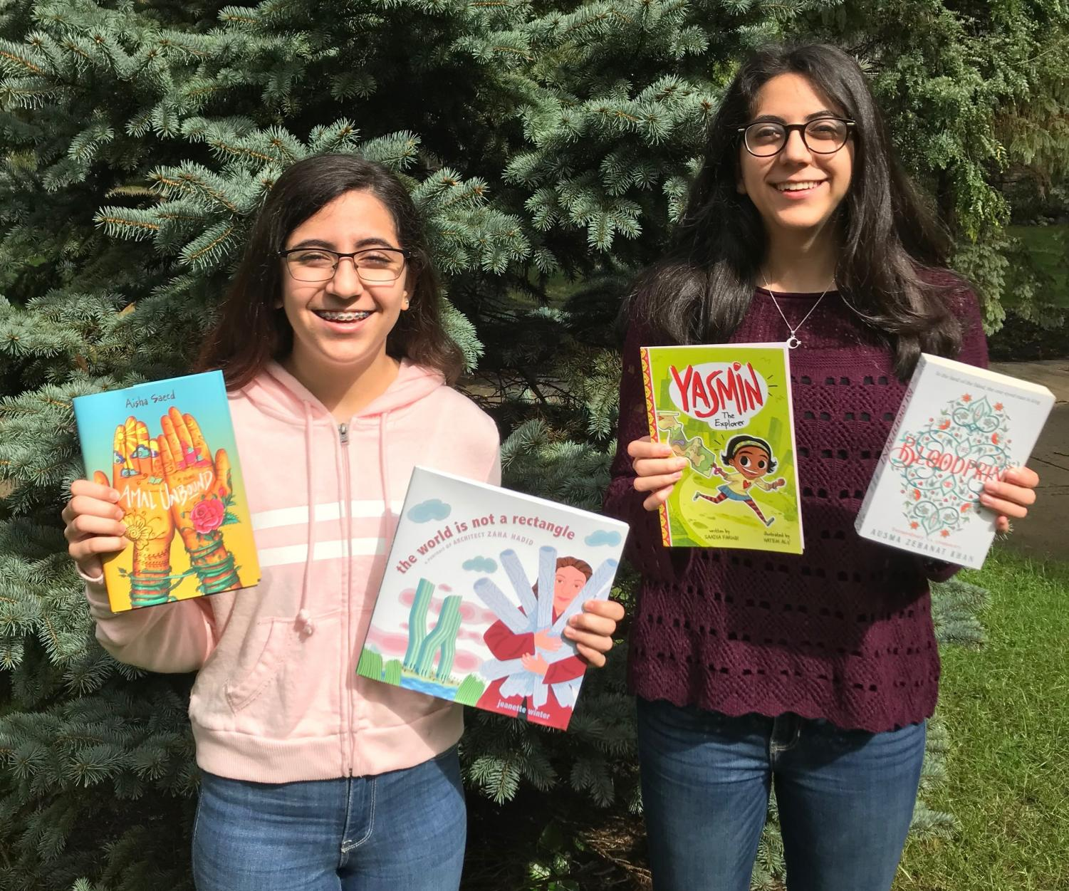 Mena (left) and Zena Nasiri (right) holding some of the books they donated.