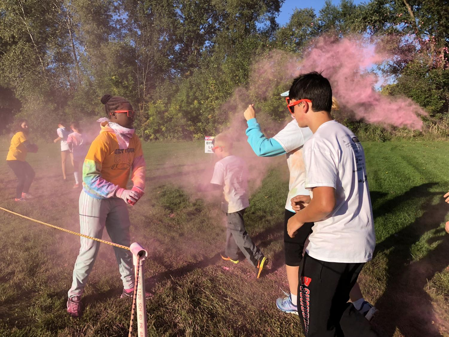 Adams students and family run through pink colored powder during the Color Run.