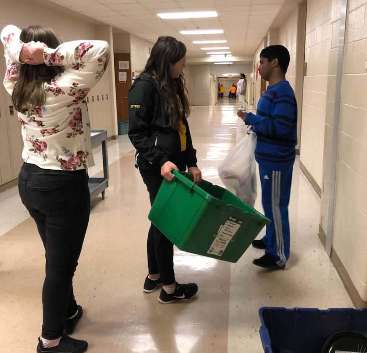 Peer mentors help students do the recycling for each classroom in the building.