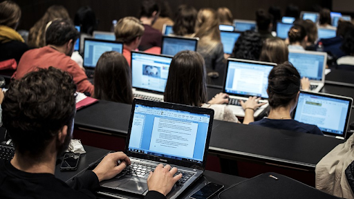 Students on laptops in class using online resources.