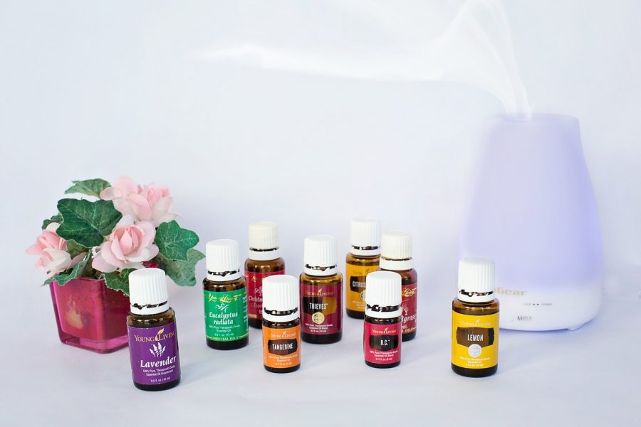 An essential oil diffuser and bottles of essential oils.