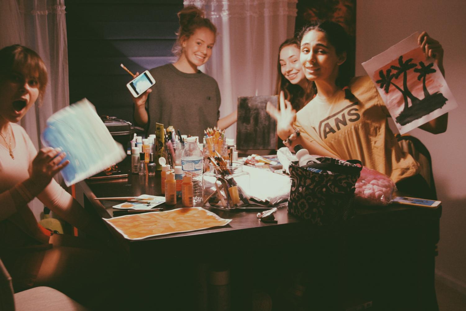 Claire Ferguson, featured far left, paints with friends on a Saturday night.