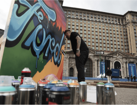 Joe Ferry spray paints a Ford picture before Ford's celebration at the station.