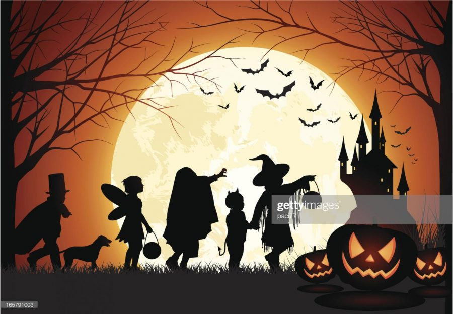 A family trick-or-treating at night.