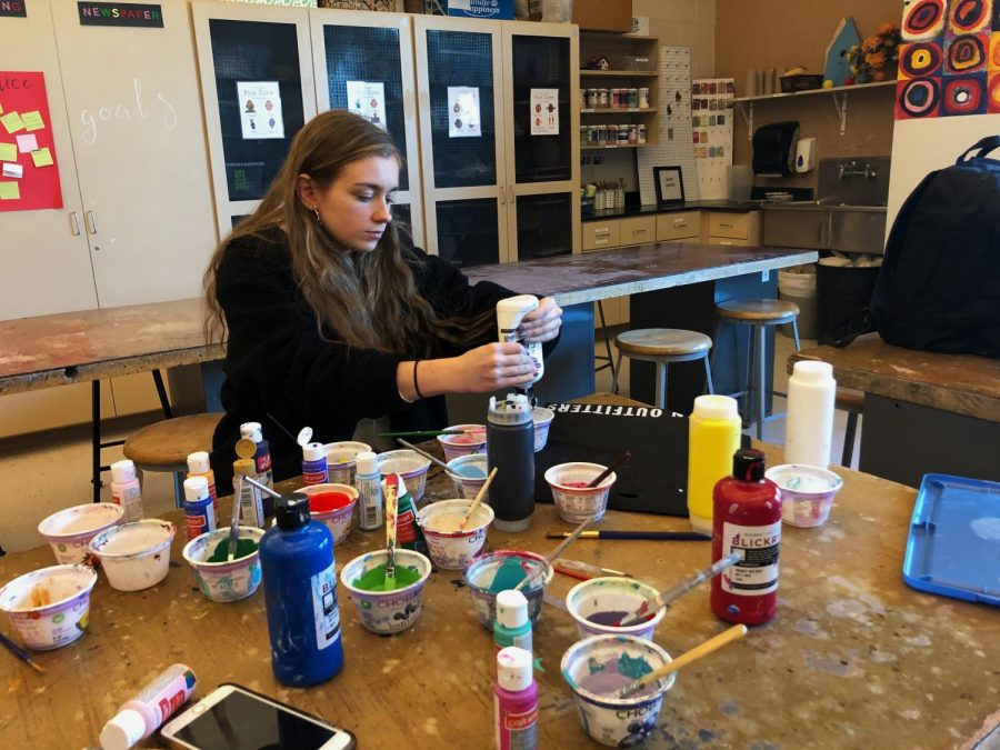 Davies works on an acrylic pour art piece using all different colors.